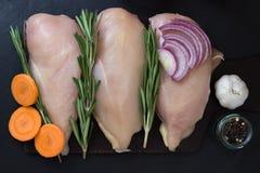 Prendedero de la pechuga de pollo con romero, las zanahorias, el ajo y las cebollas Fotografía de archivo libre de regalías