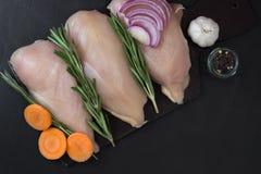 Prendedero de la pechuga de pollo con romero, las zanahorias, el ajo y las cebollas Fotografía de archivo