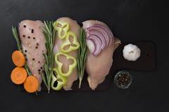 Prendedero de la pechuga de pollo con romero, y zanahorias, pimientas y cebollas tajadas Foto de archivo libre de regalías