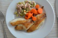 Prendedero de pescados asado a la parrilla con las sojas y el jamón en una placa blanca Foto de archivo