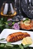 Prendedero de pescados asado a la parrilla en barbacoa con el limón contra el contexto de una copa de vino, de salmones de la ens Fotos de archivo libres de regalías