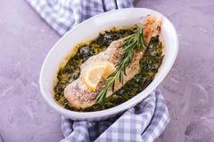 Prendedero de pescados blancos cocinado con las hierbas en espinaca frita en cocer d Imagenes de archivo