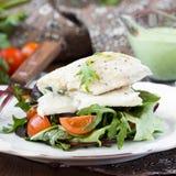 Prendedero de pescados blancos frito con la ensalada de tomates, arugula, hierbas Fotografía de archivo libre de regalías