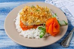 Prendedero de pescados cocido con las zanahorias debajo de una corteza del pan Imagen de archivo