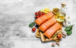 Prendedero de pescados de color salmón crudo con las especias, las hierbas y los tomates maduros imagen de archivo libre de regalías