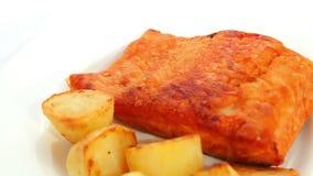 Prendedero de pescados de color salmón frito con las patatas metrajes