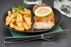 Prendedero de pescados frescos y patatas fritas en una placa Fotografía de archivo libre de regalías