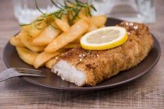 Prendedero de pescados frescos y patatas fritas en una placa Imagenes de archivo