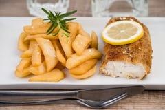 Prendedero de pescados frescos y patatas fritas en una placa Fotos de archivo