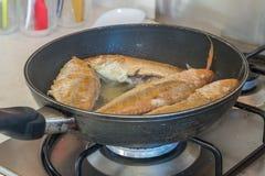 Prendedero de pescados que cocina en la cacerola de fritada, preparación de comida Imagenes de archivo