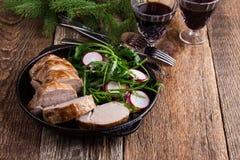 Prendedero del cerdo de carne asada con con la ensalada del arugula y del rábano Imagen de archivo libre de regalías