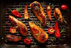 Prendederos asados a la parrilla del pollo en adobo picante con la adición del chile en una cacerola de la parrilla Foto de archivo libre de regalías