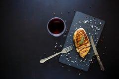 Prendederos asados a la parrilla del pollo en la placa de la pizarra con romero, vino y especias en fondo de madera oscuro Visión Imagen de archivo