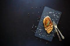 Prendederos asados a la parrilla del pollo en la placa de la pizarra con romero y especias en fondo de madera oscuro Visión super Imagen de archivo