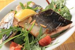 Prendederos de pescados con verdes de la ensalada y almendras tajadas Foto de archivo