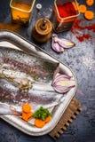Prendederos de pescados crudos con las especias, cocinando la preparación en la tabla de cocina oscura imagen de archivo libre de regalías