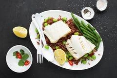 Prendederos de pescados frescos jugosos de mar blanco del vapor en un amortiguador del arroz fragante rojo y de las verduras fres Fotos de archivo libres de regalías