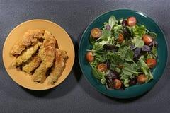 Prendederos y ensalada empanados del pollo Imagen de archivo libre de regalías