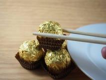 Prendendo dai bastoncini, palle del cioccolato al latte Immagine Stock