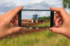 Prendendo foto del trattore sul lavoro su un campo con il telefono cellulare Fotografia Stock Libera da Diritti