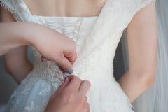 Prendendo o vestido, asseguração no vestido do ` s da noiva, taxas do botão do ` s da noiva, vestido de casamento imagens de stock