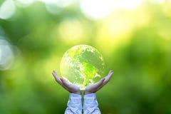 Prendendo um globo de incandescência da terra em suas mãos Fotos de Stock Royalty Free