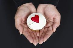 Prendendo um queque com corações do amor Foto de Stock