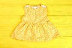 Prendisole gialle sveglie della neonata Fotografia Stock