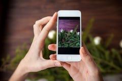 Prendre la photo avec le smartphone sur le fond en bois Photos stock