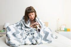 Prendre soin de chien dans la couverture chaude dans le lit Photos libres de droits