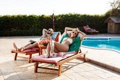 Prendre un bain de soleil d'amis, se trouvant sur des cabriolets s'approchent de la piscine Photo libre de droits