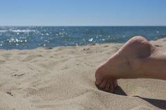 Prendre un bain de soleil sur un ventre sur une plage sablonneuse photos libres de droits