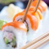 Prendre un morceau de sushi saumonés avec des baguettes Images libres de droits