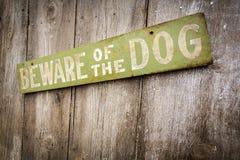 Prenez garde du chien se connectent la vieille barrière en bois utilisée image stock