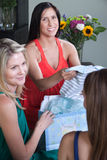 Prengnat Woman with Baby Clothes. Smiling pregnant lady with friends holds baby clothes Stock Photo