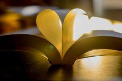Prenoti con le pagine nella forma del cuore sopra luminoso Fotografia Stock Libera da Diritti