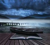 Prenoti la vecchia barca di concetto sul lago della riva con il lago nebbioso e monti Immagine Stock