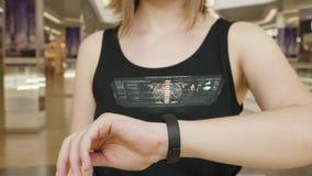 Prensa de la chica joven en la pulsera futurista del concepto de la interfaz de usuario Interfaz gráfica de usuario - GUI Exhibic almacen de video