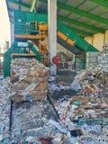 Prensa de la máquina que trabaja en el sitio del reciclaje de residuos imágenes de archivo libres de regalías