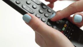 Prensa los botones en el telecontrol de la TV almacen de metraje de vídeo