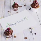 Prentbriefkaar met gelukwensen en chocolade cupcakes bessen op witte houten achtergrond lettering Art Stock Foto
