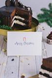 Prentbriefkaar met gelukwensen en de bessen van de chocoladecake op witte houten achtergrond lettering Art Stock Afbeelding