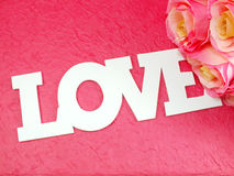 Prentbriefkaar met kunstbloemen en markering met woorden met liefde op roze achtergrond Stock Foto