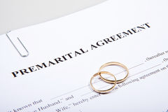 Prenuptial Agreement form and two wedding rings Stock Photos