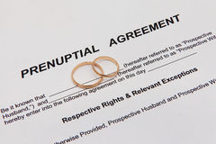 Prenuptial Agreement form and two wedding rings Stock Images