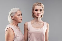 Preoccupando madre grigio-dai capelli che considera sospettoso fronte privo di emozioni fotografia stock