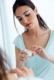 Preoccuparsi della giovane donna della sua pelle che sta specchio vicino nel bathr fotografia stock libera da diritti