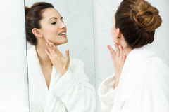 Preoccuparsi della giovane donna della sua pelle che sta specchio vicino nel bathr immagine stock