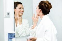 Preoccuparsi della giovane donna della sua pelle che sta specchio vicino nel bathr immagini stock libere da diritti