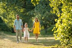 Preoccuparsi parents tenersi per mano della figlia mentre cammina insieme fotografia stock